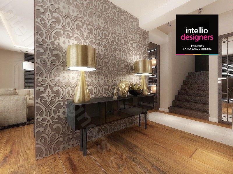 Architektura wnętrz - Projekt ściany w przepięknym domu w przedpokoju. Na ścianie zaprojektowano tapetę, komodę oraz złote lampy stojące