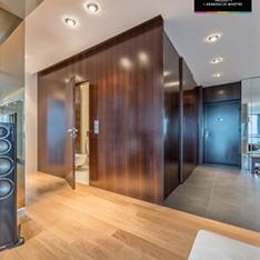 Intellio designers, widok z salonu na wejście do łazienki, ciemne drewno