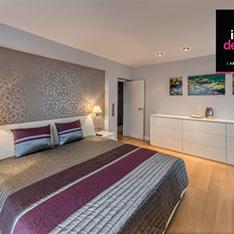 Sypialnia w mieszkaniu Ruczaj Kraków. Tapeta w sypialni, biała komoda i meble