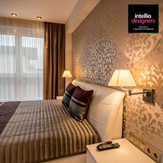 Widok sypialni, łóżko ze ściennymi lampkami nocnymi. Aranżacja wnętrz według Agnieszki Liniewskiej-Baran